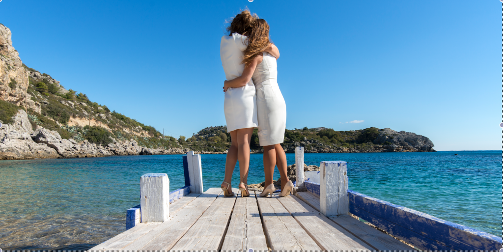 2 girls hug at the end of a small wooden pier after their gay wedding ceremony in Greece
