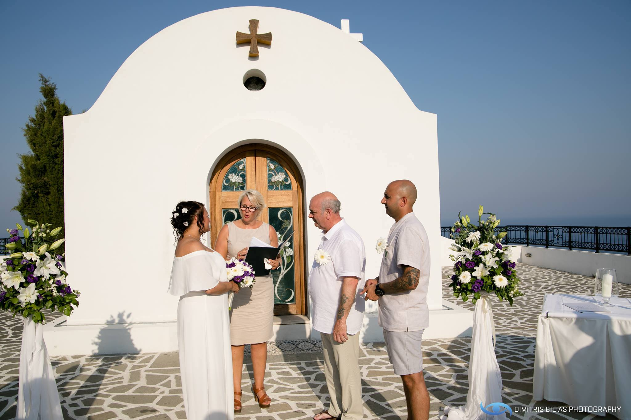 A couple stand in front of Aghia Sofia Chapel in Rhodes for their wedding ceremony in Greece. ECK - A wedding celebrant in Greece is conducting the ceremony as the son looks on.