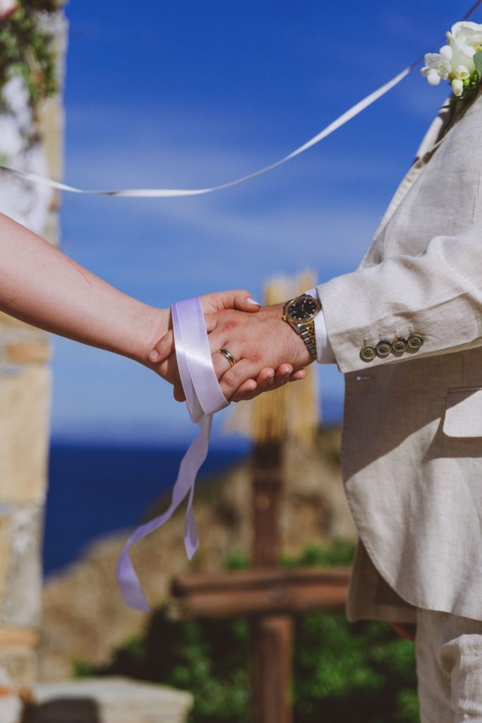 A wedding couples hands with a handfasting ribbon used during the exchange of wedding vows.