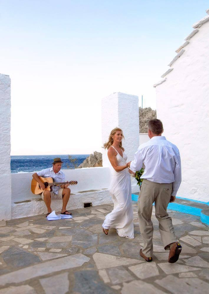 A wedding couple dance as Mark Usher, Musician and wedding DJ in Rhodes, Greece plays for them at their ceremony.