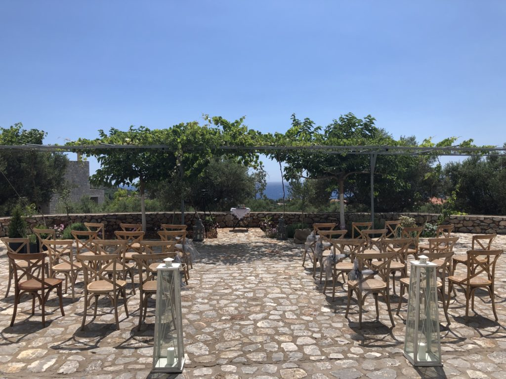 A wedding ceremony set up in Mani, Greece. Two rows of simple wooden chairs have created an aisle with a background of olive trees, and blue sea and sky.