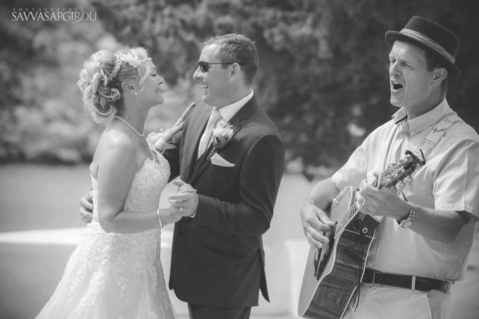 Mark Usher Musician and wedding DJ in Rhodes, Greece is singing and playing the guitar to a bride and groom