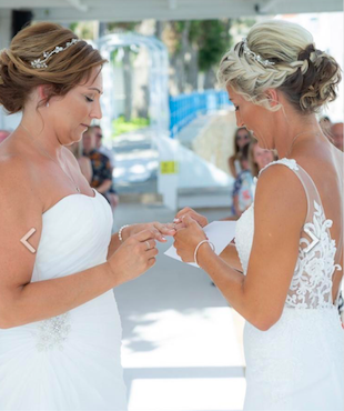 Two brides in a same sex wedding ceremony exchange wedding rings and wedding vows. The ceremony was created by ECK-A wedding Celebrant in Greece