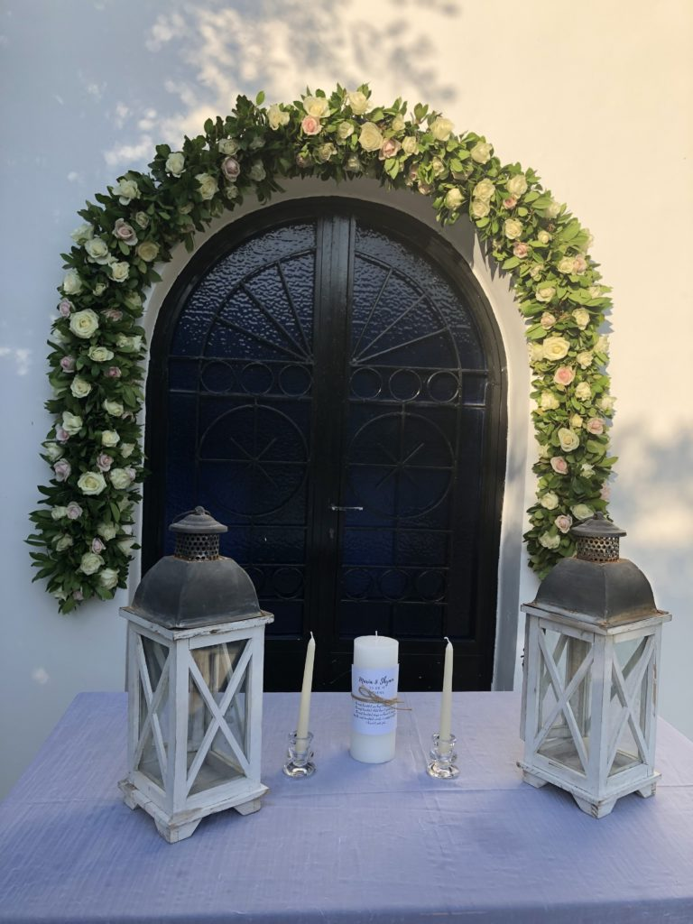 A wedding ceremony table set up in front of a greek church doorway with a green and floral reef around the door. On the table are two lanterns, two taper candles and a pillar candle which will be used for a unity candle ritual during the celebrant led wedding ceremony by ECK - a wedding celebrant in Greece.