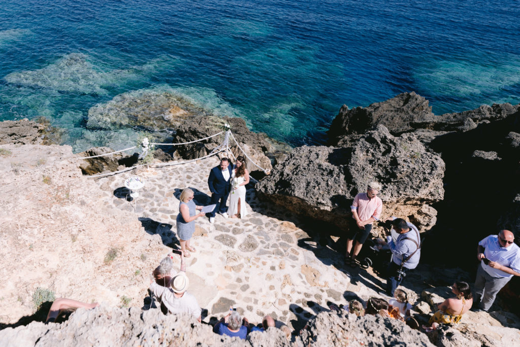 A wedding ceremony in Zakynthos, Greece. The shot taken from above shows the couple on the rocky peninsula with the blue se beyond. The wedding Celebrant in the photo is ECK, A wedding celebrant in Greece