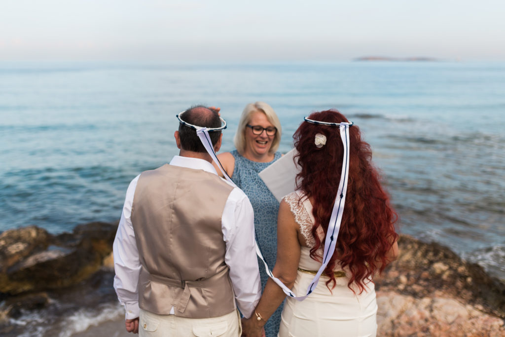 a couple face the sea wearing greek wedding corwns as they exchange their wedding vows with a celebrant in greece