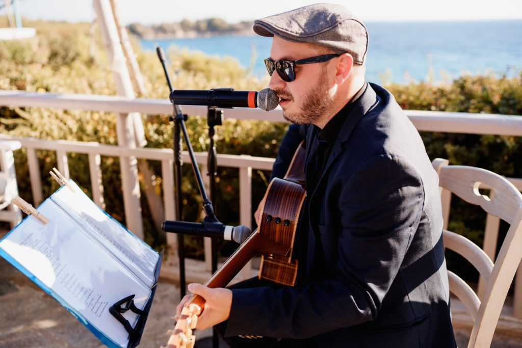 A guitar playing singer with the sea in the background at a wedding ceremony in Rhodes at Philosophia restaurant.