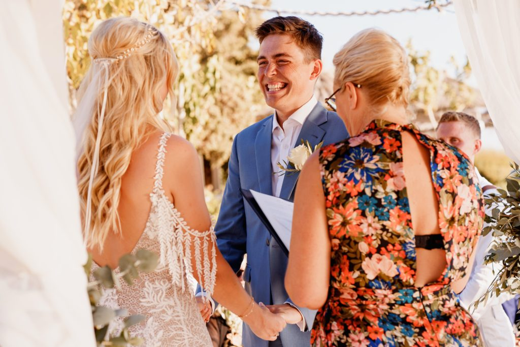 a bride and groom exchange wedding vows holding hands, with a wedding celebrant in greece