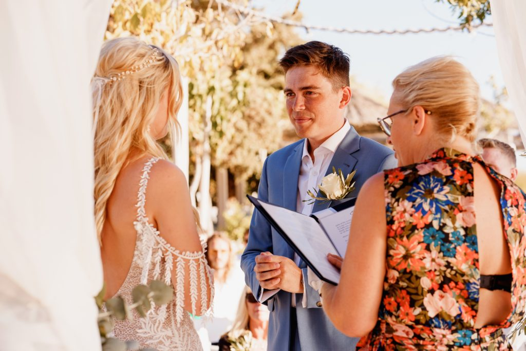 A bride and groom during their wedding ceremony with a wedding celebrant in Greece