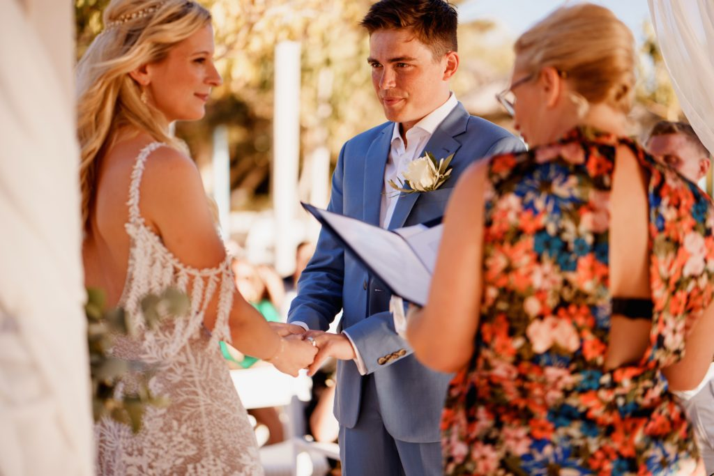 A couple holding hands and taking their wedding vows with ECK a wedding celebrant in Greece during their wedding ceremony at Philosophia.