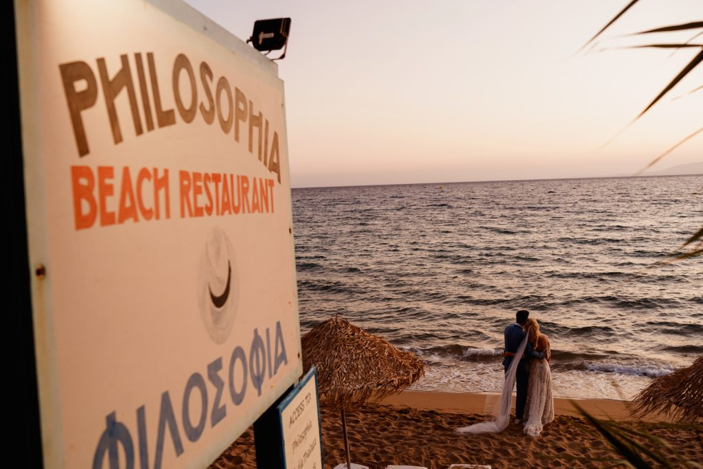 A sign showing the way down to the beach at Philosophia restaurant with a couple enjoying the view just after their wedding ceremony in Rhodes