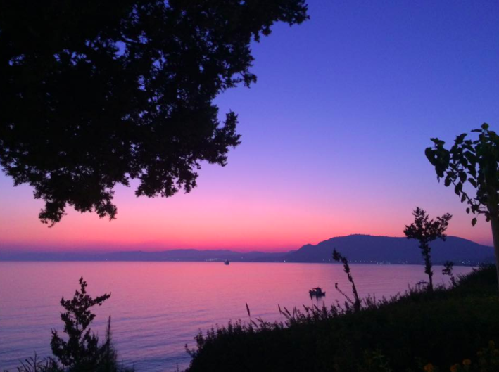 A sunset over the sea with blue and red hues, taken just after a wedding ceremony at Philosophia perfromed by ECK a wedding celebrant in Greece