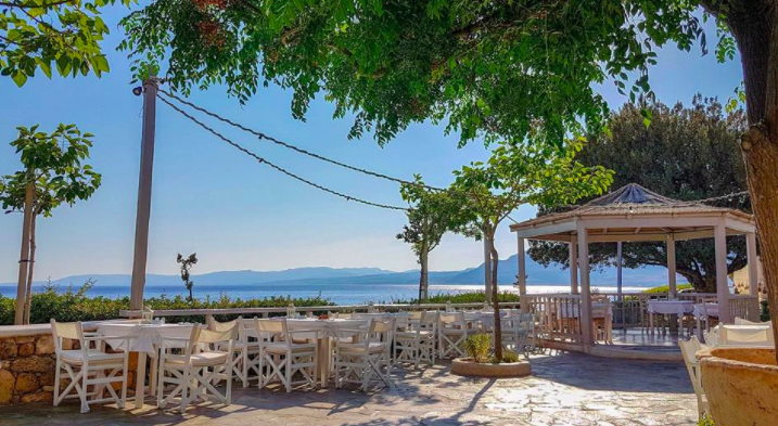 The outdoor seating area of Philosophia, Rhodes/ The blue sky and blue sea on the background are bright in the sunlight. This is a popular space for a wedding ceremony in Rhodes, Greece.