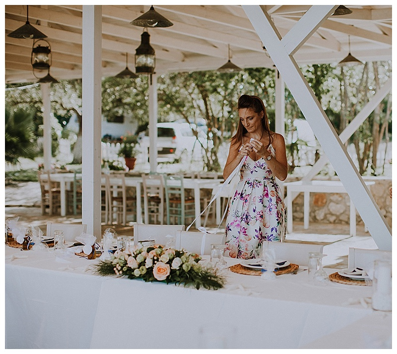 A young woman in a flowery dress is arranging flowers on a table in a greek beachside restaurant, getting ready for a wedding in lefkas