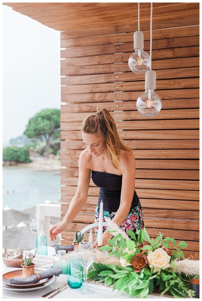 Under a wooden shelter with a pool in the background, Claire from lefkas weddings adjust a floral display getting ready for a wedding ceremony in Lefkas