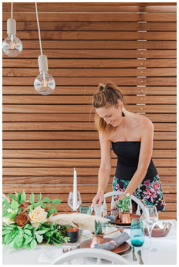 Claire from lefkas weddings puts the finishing touches to a table display, preparing for a wedding in lefkas