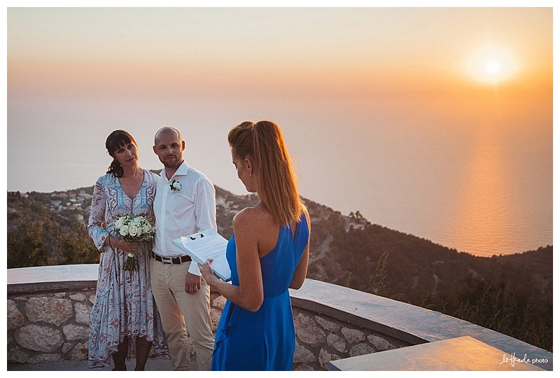 A couple stand with their backs to the sunset during a wedding ceremony in lefkas with Claire from Lefkas weddings who is in a blue dress