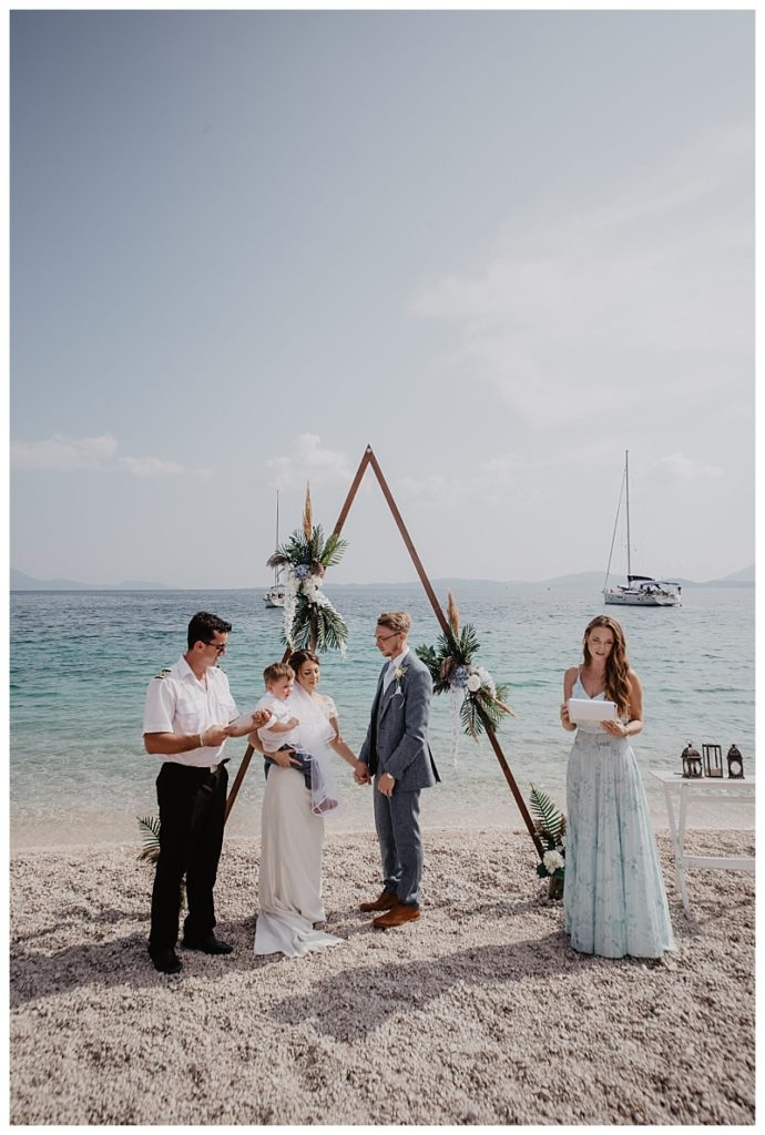 A newly wedded coupe with the registrar and claire from Lefkas weddings on a beach in Lefkas. The photo is of their wedding ceremony in lefkas