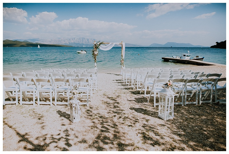 A setting for a beach wedding in Lefkas with chairs and a wedding arch on the beach with the sea in the background.