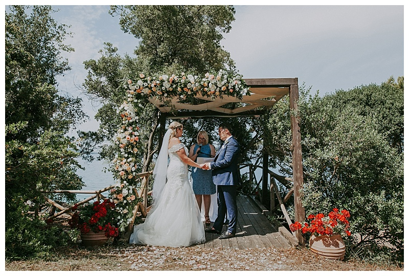 A wedding couple and Celebrant under a wooden Gazebo. There is lots of foliage and the ionian sea in the background as they exchange their wedding vows.
