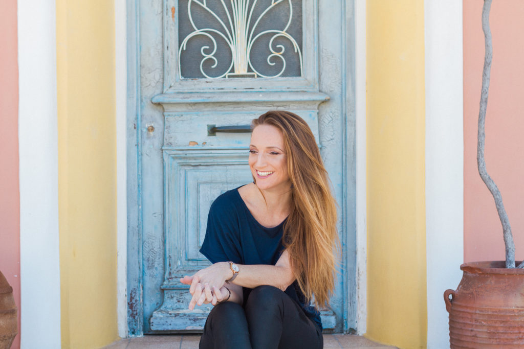a photo of a young woman with long hair sitting in a doorway with Greek pastel colours. This is Claire from Lefkas weddings, she can design your wedding in Lefkas for you!