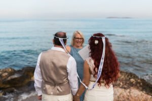 With the sea in the background, their is a wedding couple with their backs to the camera wearing Greek wedding crowns which their celebrant has placed on their heads.