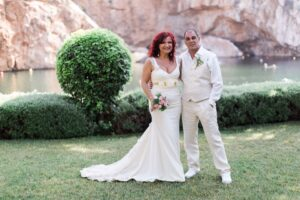A wedding portrait shot of a couple next to vouliagmeni lake in Athens after their elopement ceremony in Greece
