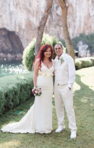A married couple on a grass verge by a lake in Athens after their elopement ceremony in Greece