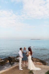 A portrait shot of a wedding couple and their celebrant by the sea during their elopement ceremony in Greece.