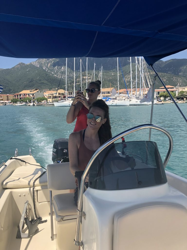 Claire from lefkas weddings driving a speedboat with Nidri, Lefkas in the background.