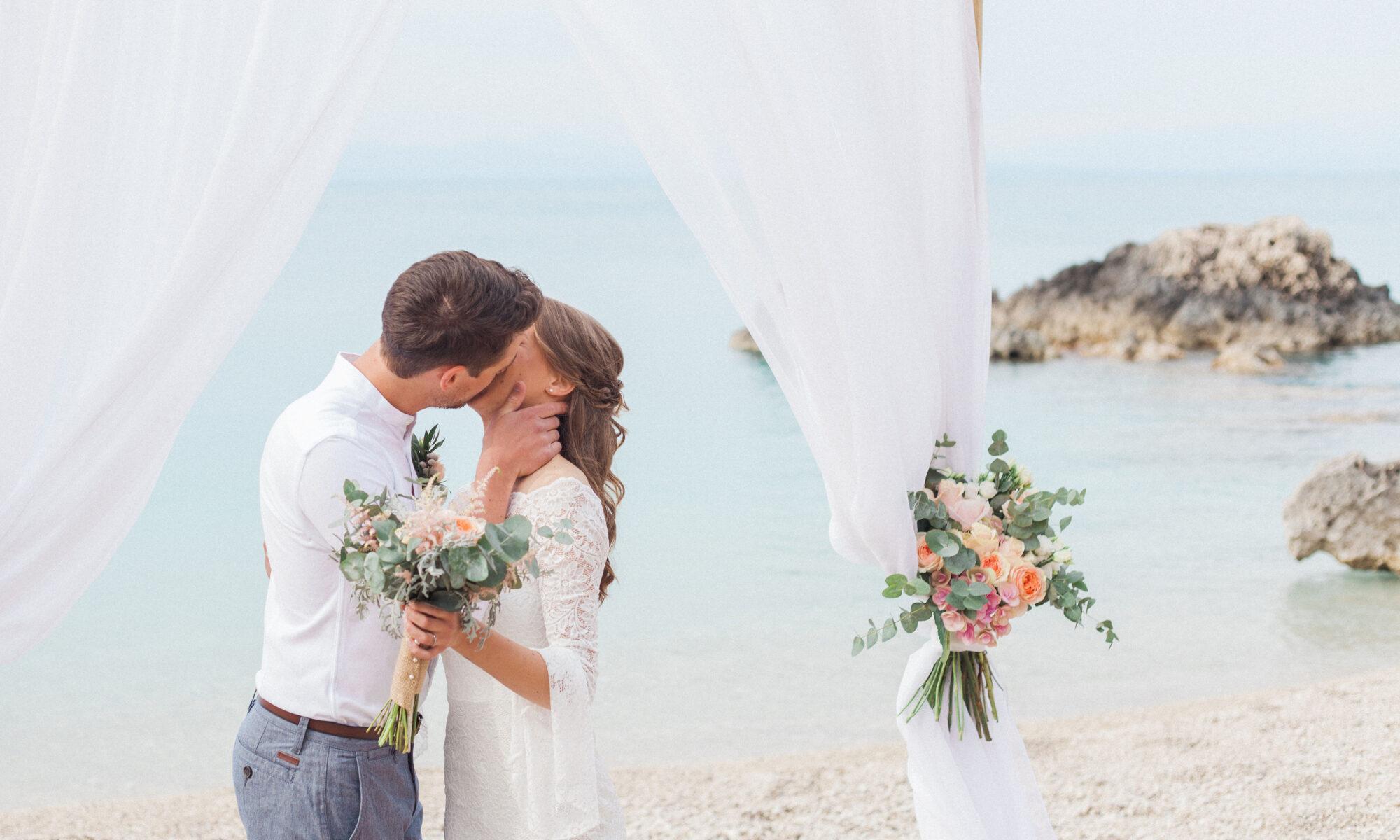 wedding couple kiss under an arch on a beautiful beach in greece